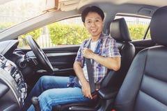Cintura di sicurezza della legatura dell'uomo dell'Asia in automobile immagini stock