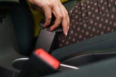 Cintura di sicurezza di sicurezza dell'automobile della legatura della donna mentre sedendosi dentro del veh fotografia stock libera da diritti