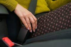 Cintura di sicurezza di sicurezza dell'automobile della legatura della donna mentre sedendosi dentro del veh immagine stock