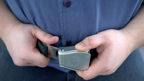Cintura di sicurezza maschio obesa della legatura del passeggero mentre sedendosi sull'aeroplano, volo sicuro immagini stock