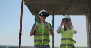 Cintura encima del retrato de dos trabajadores de construcción modernos usando el engranaje de VR para visualizar proyectos sobre metrajes