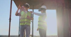Cintura encima del retrato de dos trabajadores de construcción modernos usando el engranaje de VR para visualizar proyectos sobre almacen de video