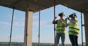 Cintura encima del retrato de dos trabajadores de construcción modernos usando el engranaje de VR para visualizar proyectos sobre almacen de metraje de vídeo