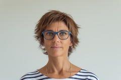 Cintura encima del retrato de la mujer adulta con los pelos rojos, ojos azulverdes, lentes y expresión facial alegre, en fondo ne Fotos de archivo libres de regalías