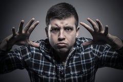 Hombre joven enojado en la camisa comprobada que nos amenaza con las manos y mirada espantosa Foto de archivo
