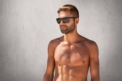 Cintura encima del retrato del hombre machista atractivo con la cerda en gafas de moda, colocándose desnudo contra la pared en bl Foto de archivo libre de regalías