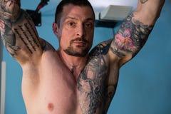 Cintura para arriba del muchacho con el cuerpo del pecho y los brazos tatuados que hacen entrenamiento del gimnasio foto de archivo