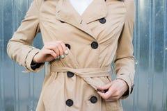 Cinturón de lazo femenino de la mano en una capa al aire libre Foto de archivo libre de regalías