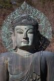Cinzeladura antiga do metal do close-up da paz de assento buddha na frente da montanha da árvore Imagem de Stock
