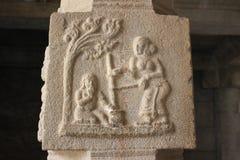 Cinzeladura da coluna da pedra do templo de Hampi Vittala do krishna do bebê que come a manteiga perto de uma árvore Imagem de Stock