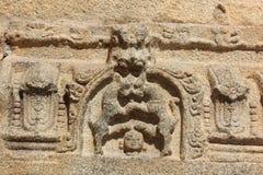 Cinzeladura do templo de Hampi Vittala da cabeça humana abaixo dos pés de dois animais selvagens de combate Imagens de Stock Royalty Free