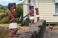 Cinzeladura maori da madeira Fileira de estatuetas do guerreiro em Whakarewarewa, Nova Zelândia imagens de stock royalty free