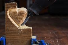 Cinzelando o coração de madeira Foto de Stock