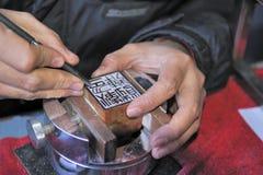 Cinzelando um selo chinês Imagens de Stock