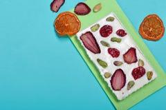 Cioccolata bianca casalinga Decorato con le fette di arancia, di fragole, di ciliege e di pistacchi secchi fotografia stock libera da diritti