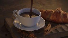 Cioccolata calda con i croissant ed i bastoni di cannella sulla tavola di lerciume stock footage