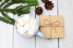 Cioccolata calda con le caramelle gommosa e molle e un contenitore di regalo su un bianco di legno Immagini Stock