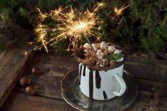 Cioccolata calda deliziosa di Natale con le caramelle gommosa e molle, i dadi e la cannella sul vassoio d'argento, fuoco selettiv Immagini Stock