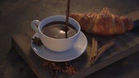 Cioccolata calda di versamento con i croissant ed i bastoni di cannella sulla tavola di lerciume archivi video
