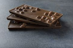 Cioccolato al latte con i dadi sulla tavola fotografie stock