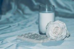 Cioccolato al latte e rosa di natura morta immagini stock