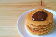 Cioccolato belga fuso che è versato sulla pila di pancake, con spazio libero sulla Tabella di legno per progettazione Immagini Stock