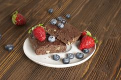 Cioccolato - brownie della ciliegia servito con il mirtillo e la fragola immagine stock libera da diritti