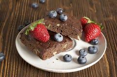 Cioccolato - brownie della ciliegia servito con il mirtillo e la fragola Fotografia Stock Libera da Diritti