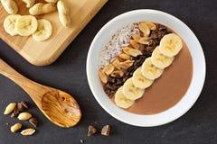 Cioccolato, burro di arachidi, banana, scena discendente della ciotola del frullato sull'ardesia immagine stock libera da diritti