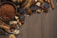 Cioccolato, cacao, dadi e spezie su fondo di legno, vista superiore immagine stock libera da diritti