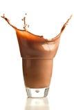 Cioccolato che spruzza nel vetro fotografie stock libere da diritti