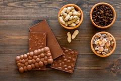 Cioccolato con i dadi sul copyspace di legno scuro di vista superiore del fondo Fotografia Stock Libera da Diritti