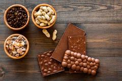 Cioccolato con i dadi sul copyspace di legno scuro di vista superiore del fondo Immagine Stock