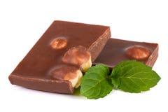 Cioccolato con le nocciole con le foglie di menta isolate su fondo bianco Fotografia Stock