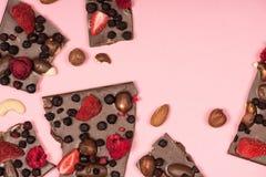 Cioccolato delizioso con i dadi e frutti isolati sul rosa Immagine Stock