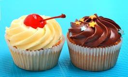 Cioccolato delizioso, muffin cremosi su fondo blu Fotografia Stock