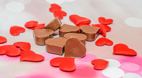 Cioccolato di forma del cuore con i cuori rossi, dolci di giorno di biglietti di S. Valentino, fondo rosa del bokeh Fotografia Stock