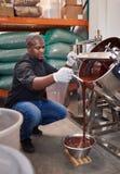 Cioccolato di fusione di versamento dell'operaio della confetteria in una ciotola immagine stock libera da diritti