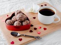 Cioccolato in un cuore rosso su un'orchidea di legno della tazza di caffè del vassoio Immagine Stock