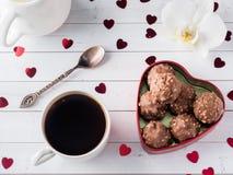 Cioccolato in un fondo di legno bianco del cuore di caffè dell'orchidea rossa della tazza Immagine Stock