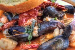 Cioppino è servito con i crostacei ed il pane all'aglio fotografia stock