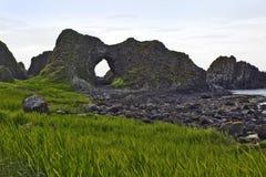 Cios dziura rzeźbił z antycznego skalistego Anrim wybrzeża blisko Balintoy schronienia Zdjęcie Stock