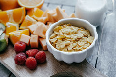Ciotola bianca con i fiocchi di mais e latte e frutta affettata fresca: Ra Fotografie Stock