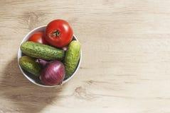 Ciotola bianca con le verdure sulla superficie di legno da sopra Immagini Stock