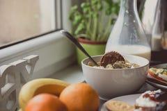 Ciotola bianca di fiocchi di granturco, fetta di banana e biscotto del cioccolato sulla cima Immagini Stock