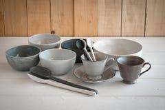 ciotola bianca e cucchiaio ceramici su un fondo grigio fotografia stock