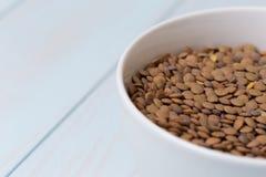 Ciotola bianca in pieno di lenticchie crude Immagini Stock Libere da Diritti