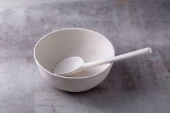 Ciotola ceramica bianca e cucchiaio dello spazio in bianco vuoto sul bordo del cemento fotografie stock libere da diritti