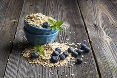 Ciotola ceramica blu in pieno di fiocco di cereali e di giardino fresco del mirtillo delle bacche su un fondo di legno scuro Fotografia Stock