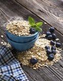 Ciotola ceramica blu in pieno di fiocco di cereali e di giardino fresco del mirtillo delle bacche su un fondo di legno scuro Immagine Stock Libera da Diritti